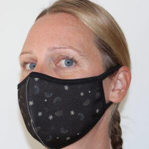 Tvättbart munskydd i svart tyg med blommar.